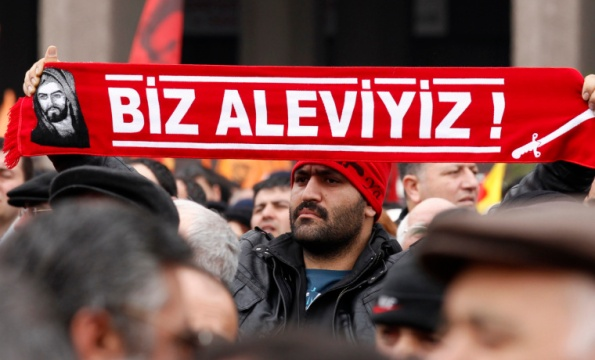 """A protester holds a banner reading """"we are alevi"""" as he and many others wait to hear the decision of the court in front of a courthouse in Ankara March 13, 2012. Turkish police fired tear-gas and water cannon to disperse hundreds protesting on Tuesday against the dropping of a case against five people charged with killing 37 writers and liberals in a 1993 hotel fire set off by Islamist rioters.The opposition accused Prime Minister Tayyip Erdogan and his AK Party, which emerged from a series of banned Islamist parties of being responsible for the failure to find the five.The case against two others charged with the kilings was dropped as the accused had died. One of them, the prime suspect who was the local mayor from the same party to which Erdogan belonged, passed away last year, close to the scene of the fire. REUTERS/Umit Bektas (TURKEY - Tags: POLITICS CIVIL UNREST)"""