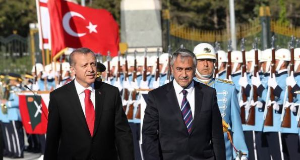 Turkish President Recep Tayyip Erdogan (L) and newly elected Turkish Cypriot leader Mustafa Akinci review an honour guard ahead of a meeting in Ankara on May 6, 2015. Akinci is a former mayor of the Turkish Cypriot half of the island's divided capital Nicosia and has been one of his community's most outspoken advocates of reconciliation with the internationally recognised Greek Cypriot government. AFP PHOTO / ADEM ALTAN
